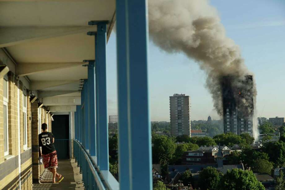 A resident in a nearby building watches smoke rise from a building on fire in London, Wednesday, June 14, 2017. A massive fire raced through the 27-story high-rise apartment building in west London early Wednesday, sending at least 30 people to hospitals, emergency officials said. (AP Photo/Matt Dunham) ORG XMIT: LMD102 Photo: Matt Dunham / Copyright 2017 The Associated Press. All rights reserved.