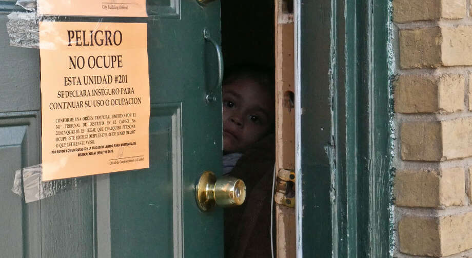 A child peaks out from a door at the Dellwood Apartments as many residents are informed that they will have to move due to the apartments they live are not up to code. Photo: Ulysses S. Romero/Laredo Morning Times
