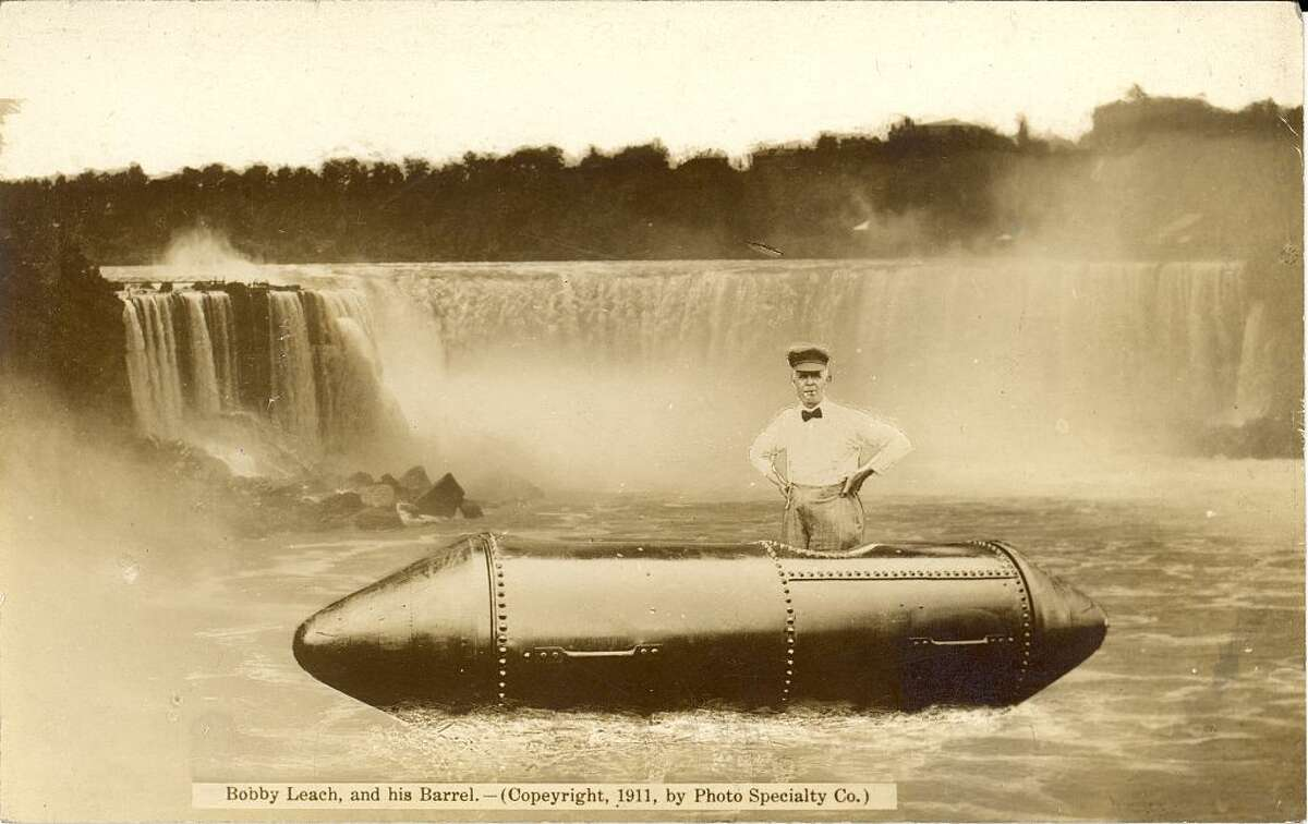 Postcard showing a composite photograph of daredevil Bobby Leach standing in the steel barrel he used to successfully go over Horseshoe Falls, July 1911. A view of the Falls appears in the background Photo Specialty Co., 1911.