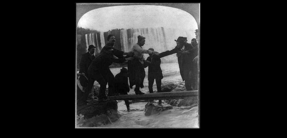 Stereograph shows Annie Edson Taylor crossing Niagara River on a plank with the falls in the distance; Mrs. Taylor was the first person to survive a trip over Niagara Falls in a barrel. M.H. Zahner.