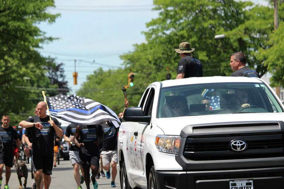 Police officers make their way into downtown Fairfield Friday as part of the Law Enforcement Torch Run for the Connecticut Special Olympics. Fairfield,CT. 6/14/17 Photo: Genevieve Reilly / Hearst Connecticut Media / Fairfield Citizen