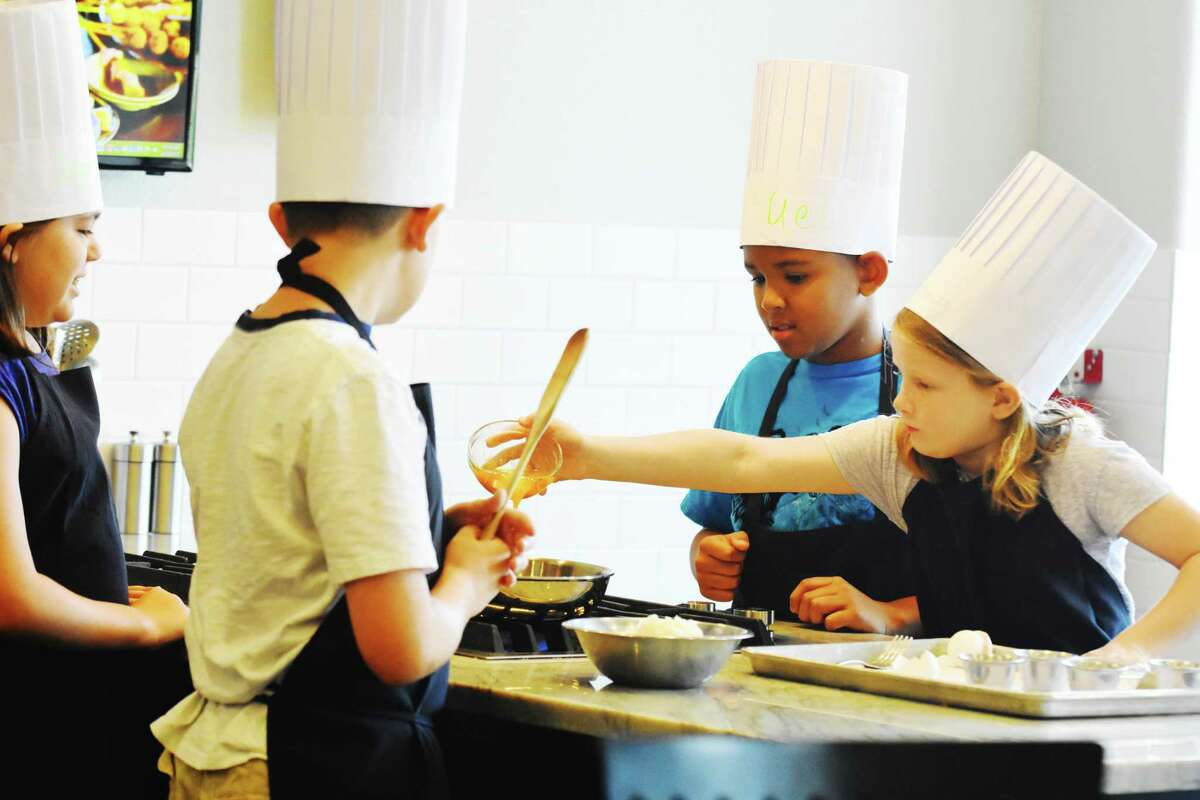In Main Street America Cooking School, kids of all ages will learn how to cultivate their self-confidence and creativity skills inside the kitchen to become young chefs. Kids also learn the skills needed to become a professional chef. From left, the cooking teamof Cole Elizondo, front, and in back Sydney Elizondo, Samual Aparicio and Rebecca Martin put the ingredients in the stir fry.