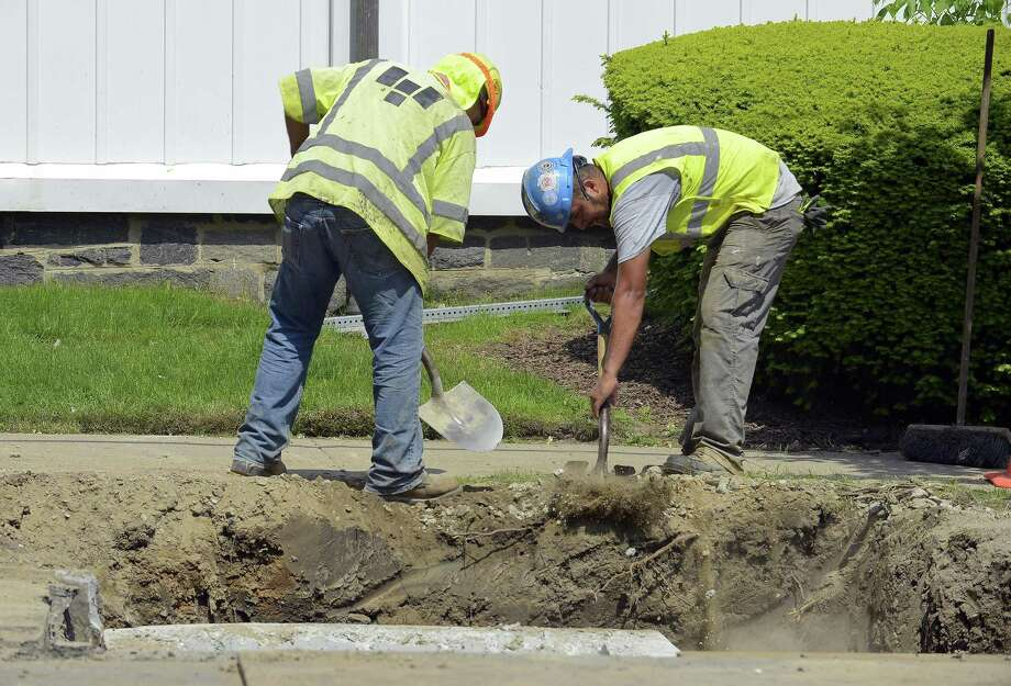 Construction workers dig in mid-May in Greenwich, Conn. Photo: Matthew Brown / Hearst Connecticut Media / Stamford Advocate