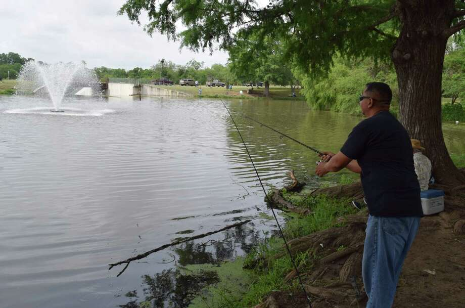 Frank Rodriguez gets his catfish-catching gear ready for a Texas Parks & Wildlife Department stocking of more than 1,000 channel cats at the lake at Southside Lions Park as part of the Neighborhood Fishin' program. Photo: Ralph Winingham /For The Express-News