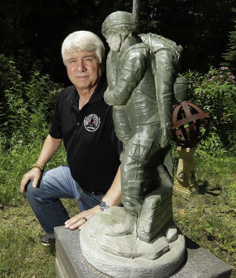 In a photo from Friday, June 9, 2017, former Army medic James McCloughan kneels next to a statue presented to him by a fellow soldier in South Haven, Mich.  An Army spokeswoman said Tuesday, June 13 that McCloughan, who saved the lives of 10 soldiers during the Battle of Nui Yon Hill in May 1969 in Vietnam, will become the first person to be awarded the nation's highest military honor by President Donald Trump. (AP Photo/Carlos Osorio) Photo: Carlos Osorio, STF / Associated Press / Copyright 2017 The Associated Press. All rights reserved.