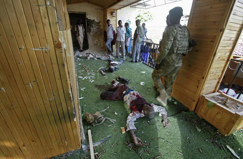 """Somali soldiers and others stand near the bodies of some of the al-Shabab attackers at the scene of a car bomb blast and gun battle targeting a restaurant in Mogadishu, Somalia Thursday, June 15, 2017. Somalia's security forces early Thursday morning ended a night-long siege by al-Shabab Islamic extremists at the popular """"Pizza House"""" restaurant in the capital. (AP Photo/Farah Abdi Warsameh) Photo: Farah Abdi Warsameh, STR / Associated Press / Copyright 2017 The Associated Press. All rights reserved."""