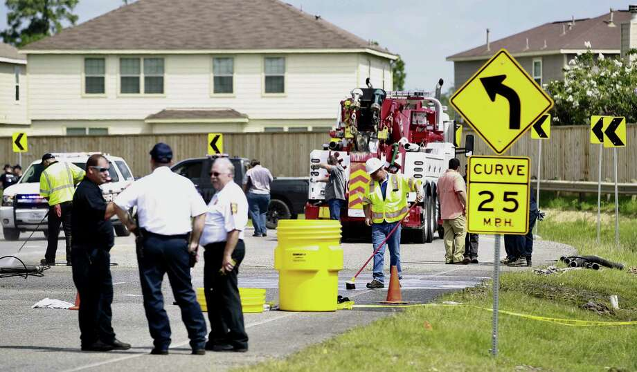 Workers clear the scene of debris after an 18-wheeler carrying hazardous materials overturned on Rayford Road, Thursday, June 15, 2017, in Spring. Photo: Jason Fochtman, Staff Photographer / Conroe Courier / HCN