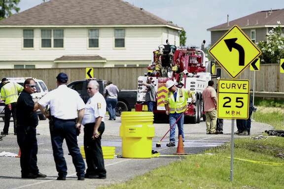 Workers clear the scene of debris after an 18-wheeler carrying hazardous materials overturned on Rayford Road, Thursday, June 15, 2017, in Spring.