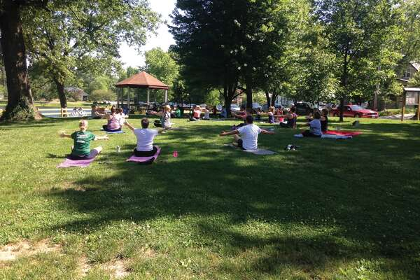 A group follows the lead of instructor Donna Bartley during Saturday's Yoga in the Park session at Leclaire Park. Free yoga is offered through the Edwardsville Parks and Recreation Department every Saturday through the summer at 9 a.m. on the Madison Avenue side of the park.