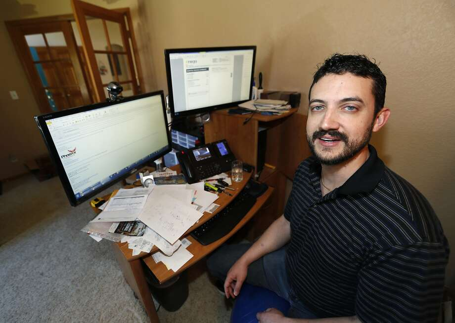 In this Wednesday, June 14, 2017, photograph, Danny Aguilar poses from his office in his home in Lakewood, Colo. Aguilar, like nearly half of Americans surveyed in a new poll conducted by The Associated Press-NORC Center Public Affairs Research, said they will not be taking a vacation this summer because they can not afford it or can not get time away from the job. (AP Photo/David Zalubowski) Photo: David Zalubowski, Associated Press