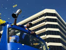 Kevin Durant holds up the NBA MVP trophy in downtown Oakland, Calif. as thousands of fans watch the Warriors Championship Parade on Thursday, June 15, 2017.