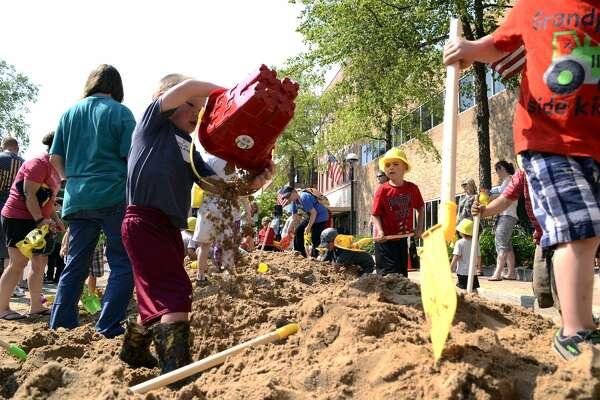 "Kids play in a sand pile on Main Street during the ""Dig In Midland"" kick-off event on Wednesday."