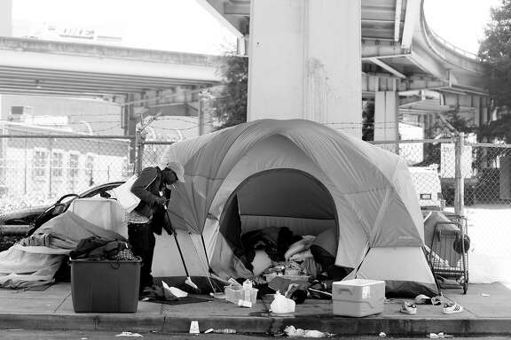 Mayweather sweeps up in front of her tent as she salvages her belongings after she and her partner broke up in San Francisco. & Homeless take different paths after SF street camp shut down