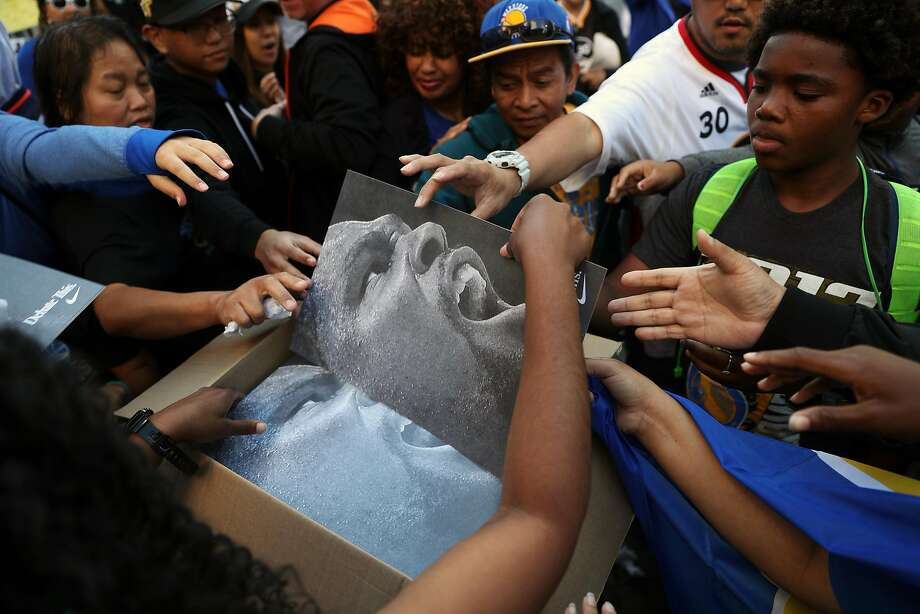 Golden State Warriors' fans grab for Kevin Durant posters before championship parade on Broadway in Oakland, Calif., on Thursday, June 15, 2017. Photo: Scott Strazzante, The Chronicle