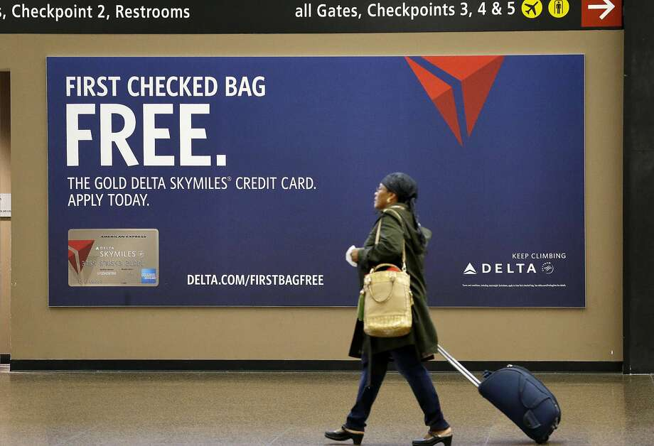 FILE - In this Tuesday, March 24, 2015, file photo, a traveler walks past a sign advertising a Delta credit card at Seattle-Tacoma International Airport in SeaTac, Wash. Photo: Elaine Thompson, Associated Press