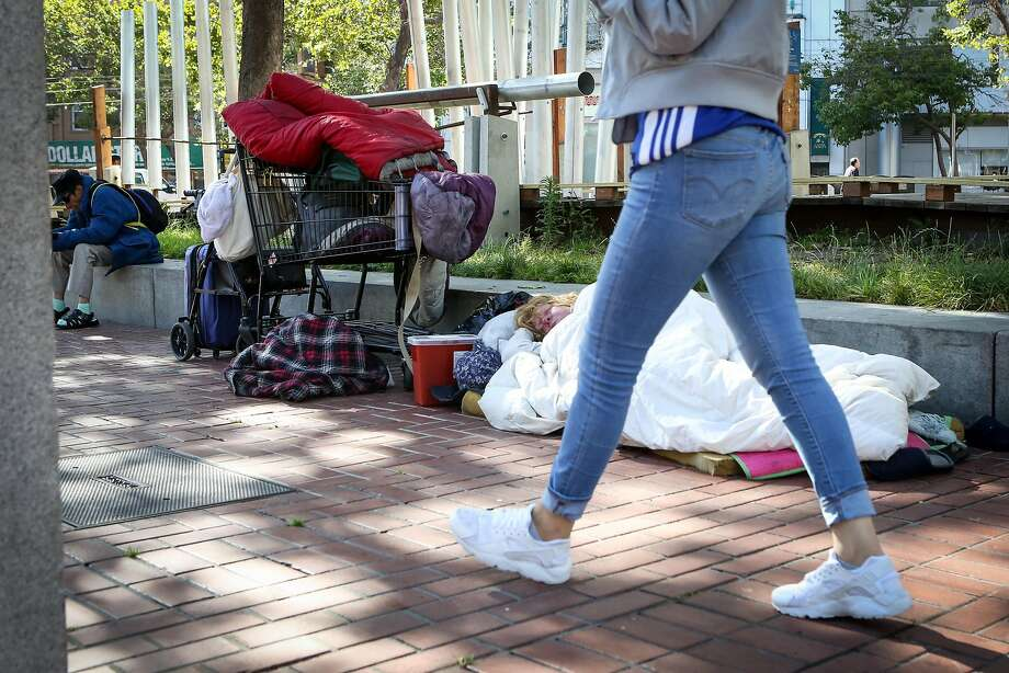 A homeless woman sleeps on the pavement near Civic Center in June. Mayor Ed Lee, who died last week, made addres sing home less ness a priority. Residents hope the city will continue that work. Photo: Amy Osborne, Special To The Chronicle