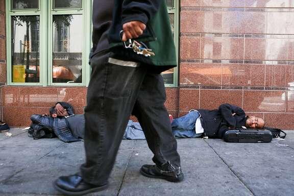A man walks past two homeless men sleeping on the sidewalk on Ellis Street, an area known for it's chronic homeless encampments on Thursday, June 15, 2017 in San Francisco, Calif.