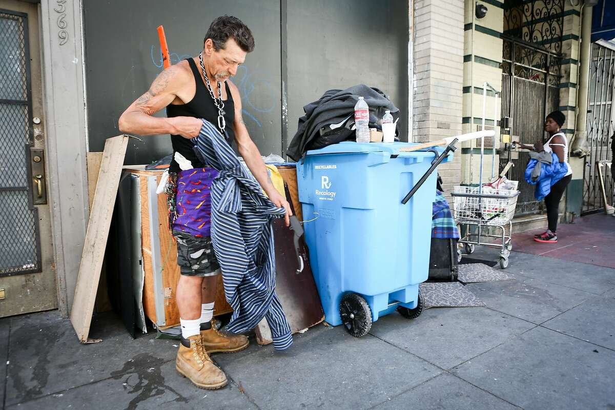 Vernon Guywells Jr. straightens out his shirt to put on a hanger to hang with his stuff on Ellis street on Thursday, June 15, 2017 in San Francisco, Calif. Guywells has been homeless for five years.