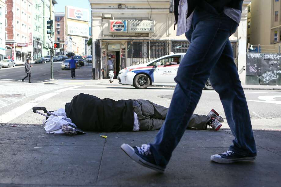 A homeless man sleeps on the sidewalk on Ellis and Jones in San Francisco, an area known for its encampments of chronically homeless people. Photo: Amy Osborne / Special To The Chronicle