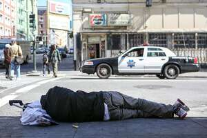 A homeless man sleeps on the sidewalk on Ellis Street and Jones, an area known for it's chronic homeless encampments, while a police car passes by on Thursday, June 15, 2017 in San Francisco, Calif.