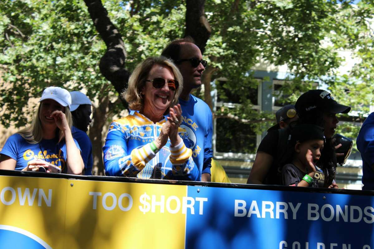 Robin Schreiber, AKA Sweater Mom, rides aboard a parade float during the Warriors Victory parade in Oakland on June 15, 2017.