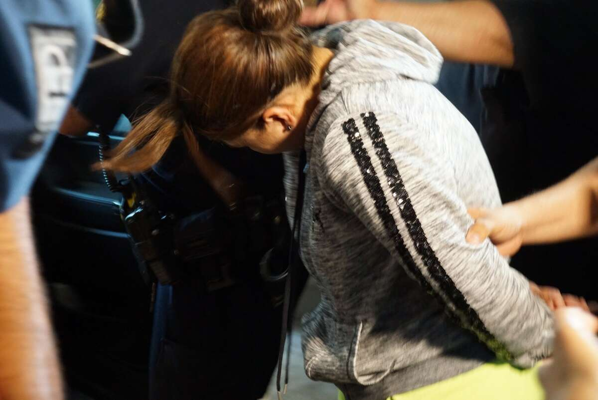 Stephanie Carmona, 34, is taken in handcuffs Tuesday afternoon, June 15, 2017, to a squad vehicle by San Antonio Police Department officers at the San Antonio Public Safety Headquarters, 315 S. Santa Rosa Ave. She faces a charge of continuous sexual abuse of a child.