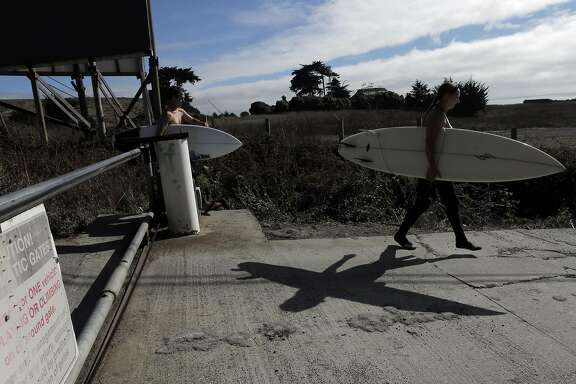 Surfers Nick Nayfack, of San Francisco, left, and Taletha Derrington, right of Belmont, go around a gate blocking Martin's Beach Road at Martin's Beach in San Mateo County, Calif., on Wednesday, September 24, 2014. A judge ruled on Wednesday, that property owner Vinod Khosla has to reopen the road that provides public access to the public beach.
