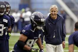 Seattle Seahawks head coach Pete Carroll, right, smiles as he watches Doug Baldwin run a drill during NFL football practice Thursday, June 15, 2017, in Renton, Wash. (AP Photo/Elaine Thompson)