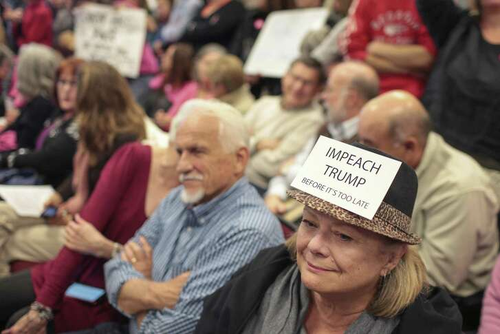 "Lynn Meek wears a sign that reads ""Impeach Trump Before it's too late"" during an open meeting in Greensboro, Ga. The calls for impeachment have been feverish and over the top even before Trump's firing of FBI director James Comey."