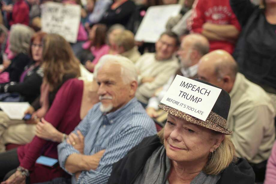 "Lynn Meek wears a sign that reads ""Impeach Trump Before it's too late"" during an open meeting in Greensboro, Ga. The calls for impeachment have been feverish and over the top even before Trump's firing of FBI director James Comey. Photo: John Roark /Associated Press / Athens Banner-Herald no sales no mags"