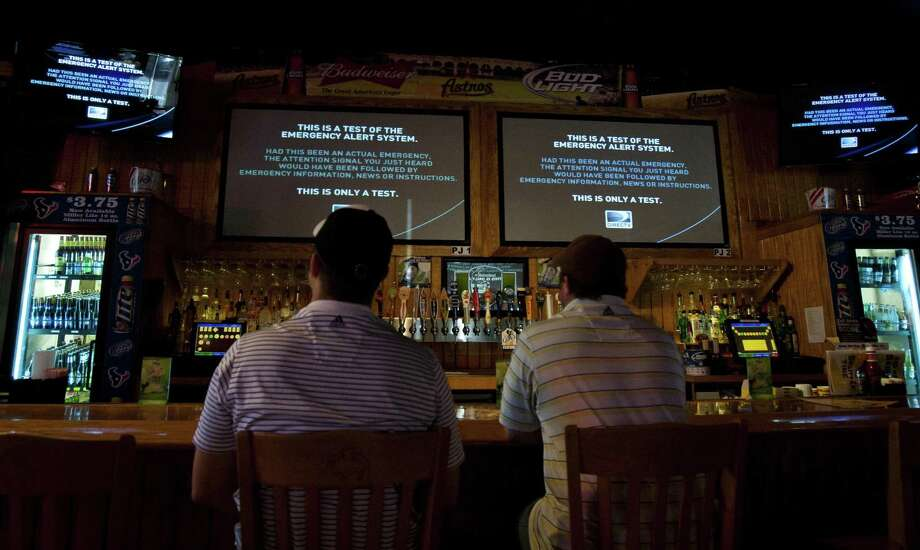 Patrons at a Houston restaurant watch a test of the Emergency Alert System in 2011 during their lunch break. The FCC fined a Jacksonville, Fla., TV station for emulating the emergency alert system for commercial purposes. Photo: Houston Chronicle File Photo / © 2011 Houston Chronicle