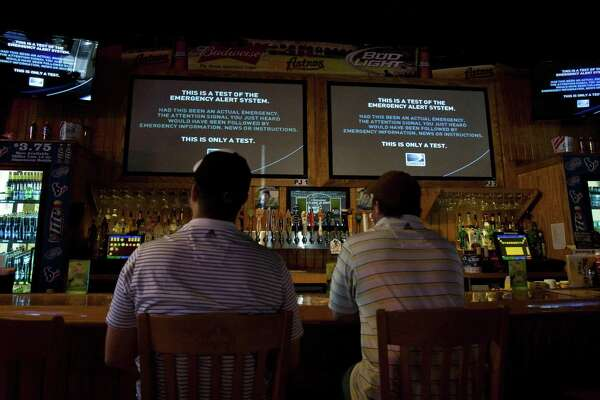 Patrons at a Houston restaurant watch a test of the Emergency Alert System in 2011 during their lunch break. The FCC fined a Jacksonville, Fla., TV station for emulating the emergency alert system for commercial purposes.