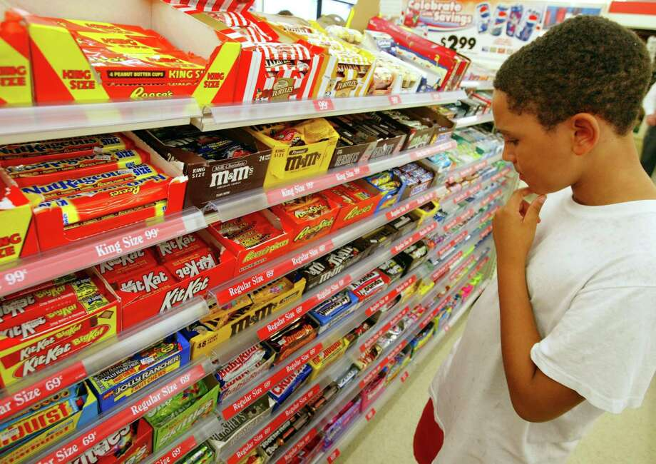 A shopper ponders candy options at a 7-Eleven store in Pembroke Pines, Fla. On June 15, 2017, Nestle announced it is considering the sale of its U.S. confectionary business to include brands like Butterfinger, Gobstoppers and SkinnyCow, while retaining KitKat and Toll House. Photo: Joe Raedle / Joe Raedle /Getty Images / 2002 Getty Images