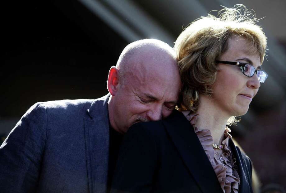 TUCSON, AZ - MARCH 06:(BEST OF 2013 PACKAGE)   Mark Kelly leans his head on the shoulder of his wife and former Congresswoman Gabby Giffords as they attend a news conference asking Congress and the Senate to provide stricter gun control in the United States on March 6, 2013 in Tucson, Arizona. Giffords and Kelly were joined by survivors of the Tucson shooting as they spoke outside the Safeway grocery store where the shooting happened two years ago where six people were killed. (Photo by Joshua Lott/Getty Images) Photo: Joshua Lott, Stringer / Getty Images / ONLINE_CHECK