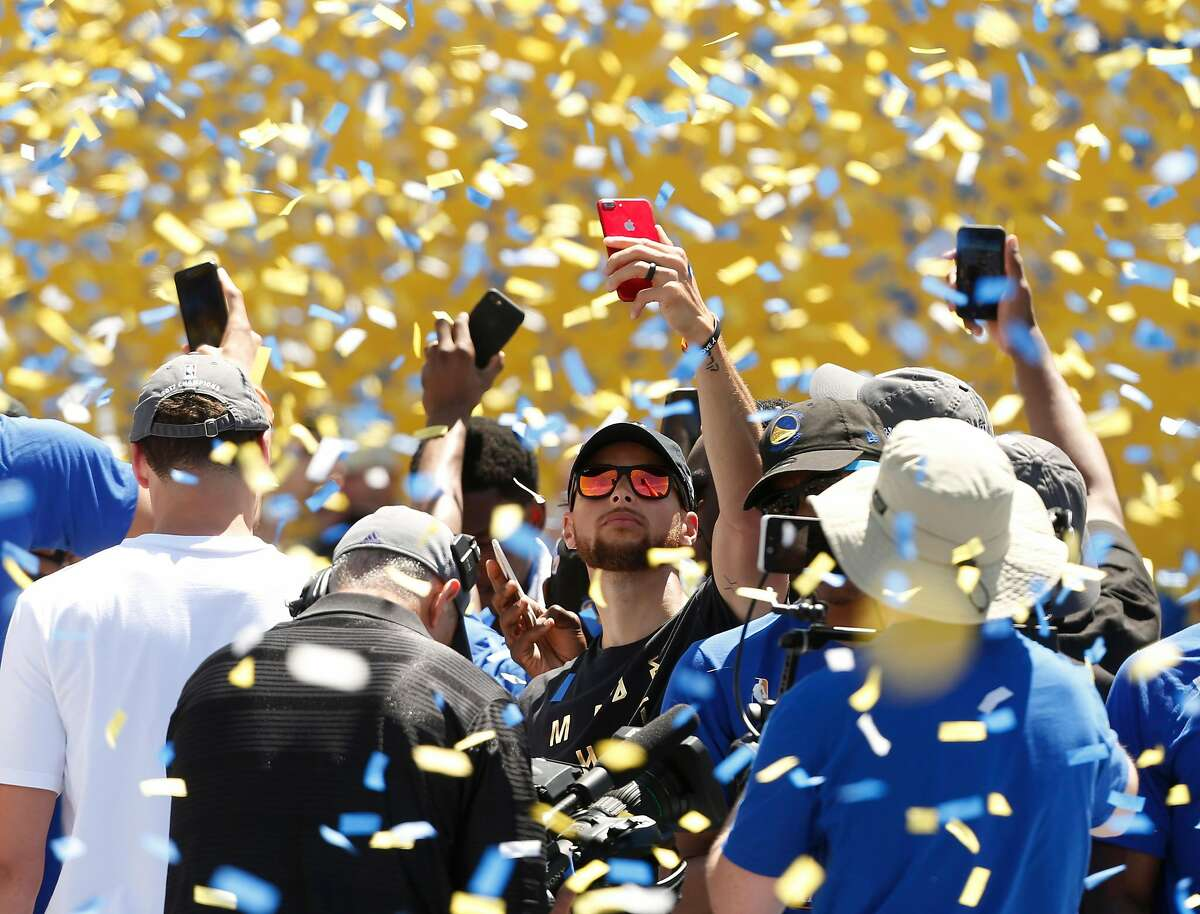 Stephen Curry snaps a selfie with confetti falling at the Golden State Warriors victory rally in Oakland, Calif. on Thursday, June 15, 2017.
