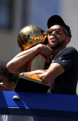 Stephen Curry holds the Larry O'Brien Trophy as the Golden State Warriors celebrated their NBA Championship with a victory parade in Oakland, Calif., on Thursday, June 15, 2017.