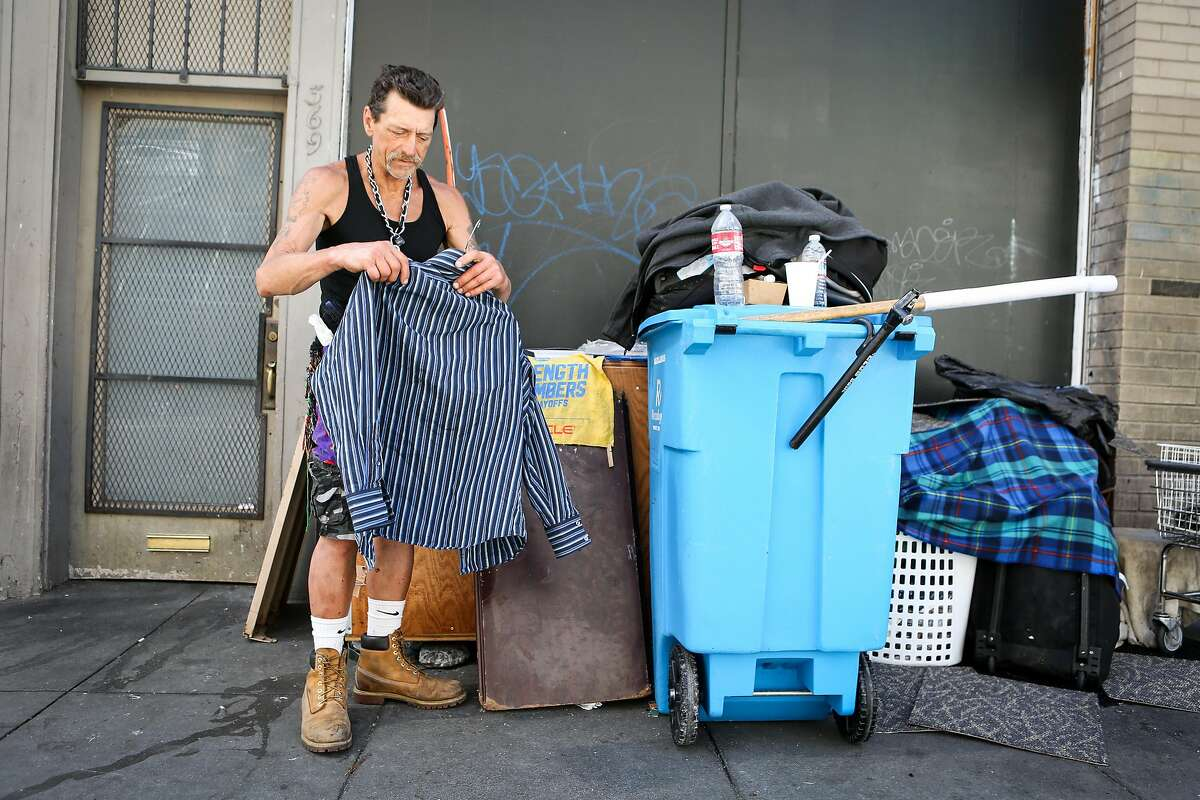 Vernon Guywells Jr. puts his shirt on a hanger to hang it with his stuff on Ellis street on Thursday, June 15, 2017 in San Francisco, Calif. Guywells has been homeless for five years.