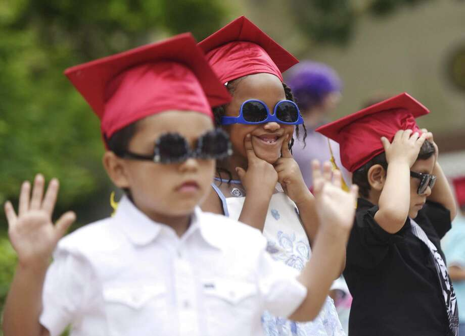 New preschool graduates Lucas Valverde, left, Arielle Mills and Gian-Pierre Portilla dance along to music after receiving their diplomas at the Family Centers Head Start preschool graduation ceremony at Armstrong Court in the Chickahominy section of Greenwich, Conn. Thursday, June 15, 2017. Photo: Tyler Sizemore / Hearst Connecticut Media / Greenwich Time