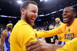 Golden State Warriors' Stephen Curry and Andre Iguodala react at end of Warriors' 129-115 win over San Antonio Spurs during Game 4 of NBA Western Conference Finals at AT&T Center in San Antonio, Texas, on Monday, May 22, 2017.