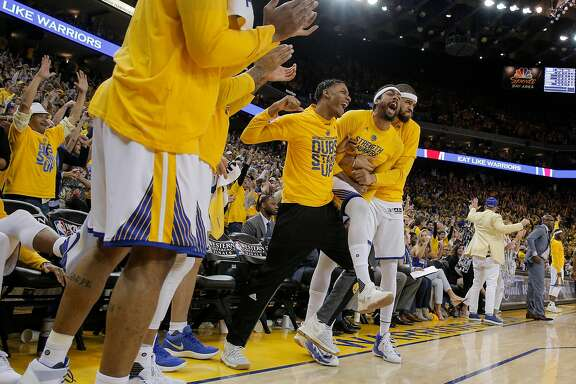 Golden State Warriors' Patrick McCaw, center, James Michael McAdoo, and JaVale McGee celebrate on the bench in the fourth quarter during Game 1 of the 2017 NBA Playoffs Western Conference Finals at Oracle Arena on Sunday, May 14, 2017 in Oakland, Calif.