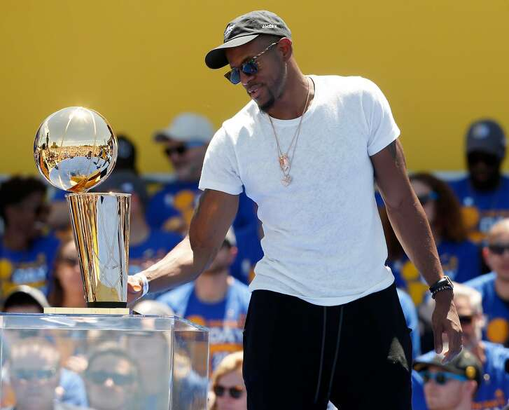 Andre Iguodala touches the Larry O'Brien trophy at the Golden State Warriors victory rally in Oakland, Calif. on Thursday, June 15, 2017.