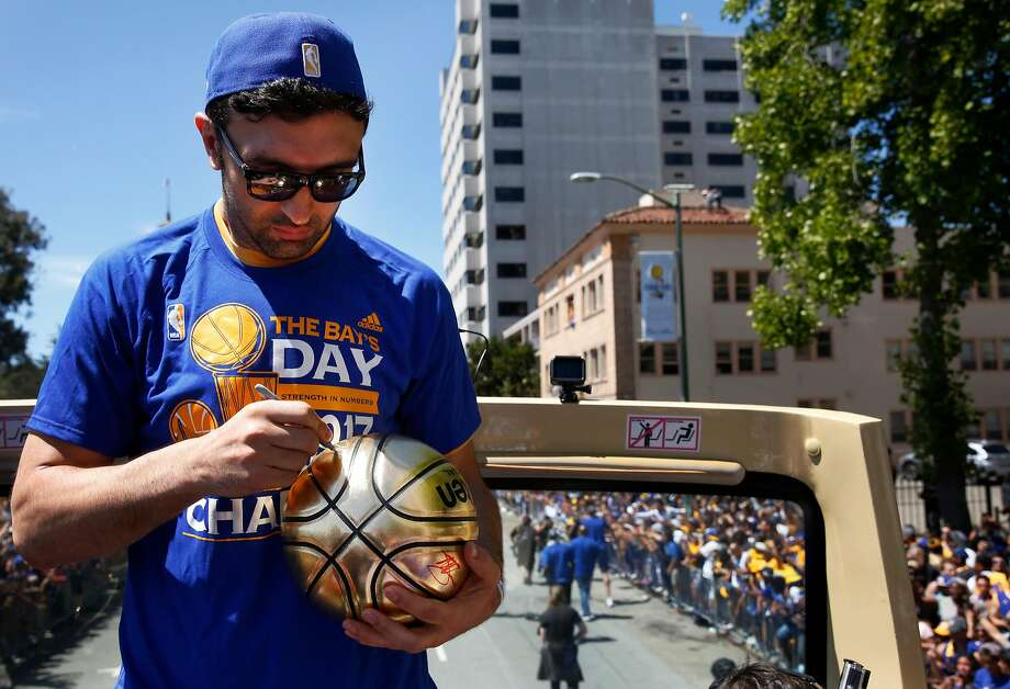 Zaza Pachulia signs a ball thrown to him from a fan during the Warriors' 2017 NBA Championship parade June 15, 2017 in Oakland, Calif. Photo: Leah Millis, The Chronicle