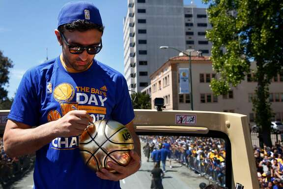 Zaza Pachulia signs a ball thrown to him from a fan during the Warriors' 2017 NBA Championship parade June 15, 2017 in Oakland, Calif.