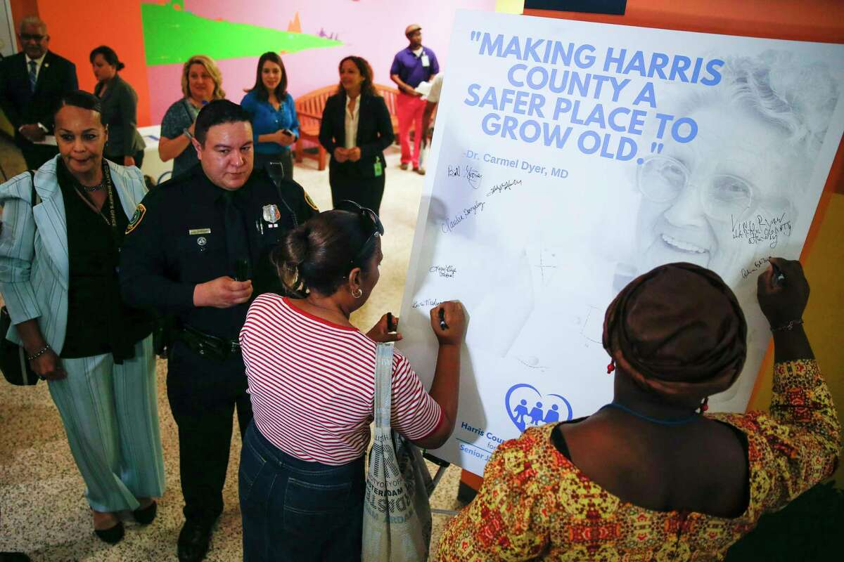 Court liaison Gwendolyn Meshack, left, and guardianship supervisor Aline Kyle-Taylor sign a pledge to keep seniors safe at the launch of the Harris County Senior Justice Assessment Center.