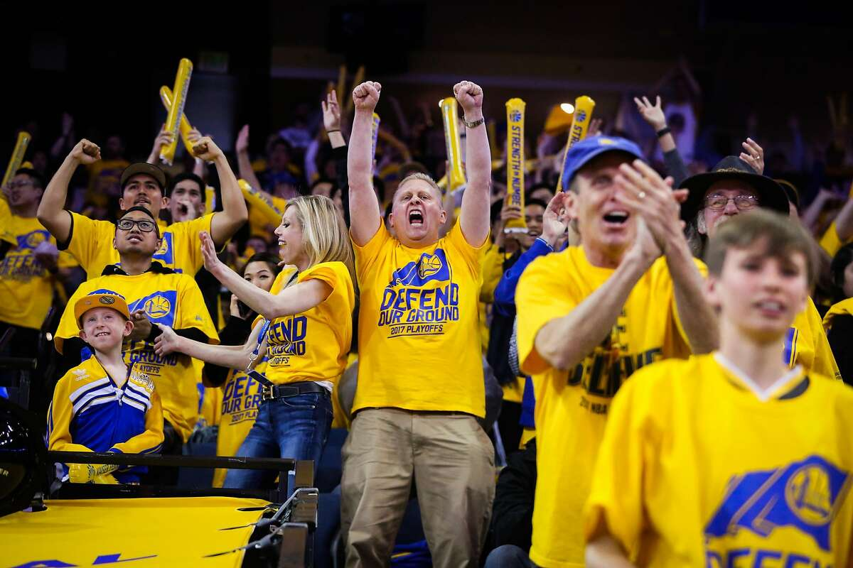 Fan Mike Zawadski (center) cheers during a play in the first half an NBA playoff game between the Golden State Warriors and the Portland Trailblazers in Oakland, California, on Sunday, April 16, 2017.
