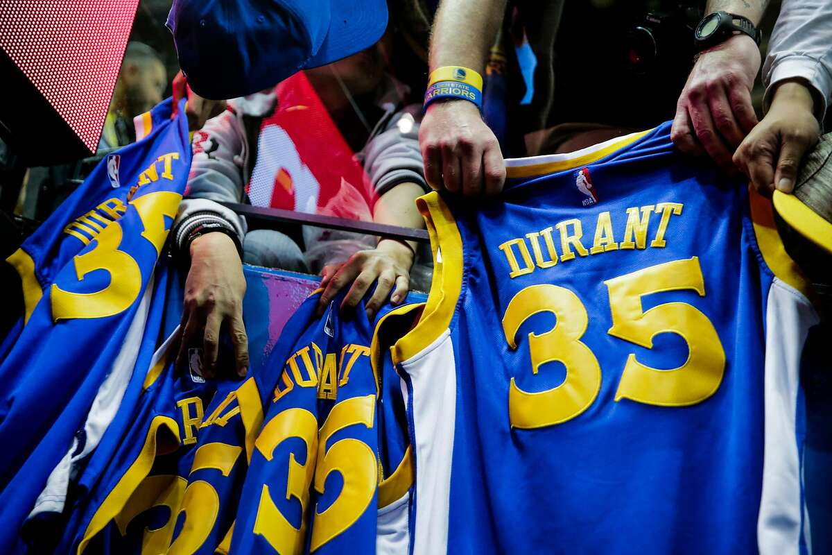 Golden State Warriors fans hold out Kevin Durant (35) jerseys as they wait for autographs ahead of a game against the Washington Wizards at Oracle Arena in Oakland, Calif., on Sunday, April 2, 2017.