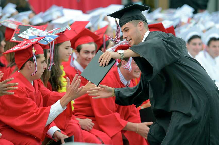 Jackson Nuzzaci high fives fellow classmates as he celebrates his graduation from Fairfield Warde High School during Commencement Exercises at the school in Fairfield, Conn., on Thursday, June 15, 2017.