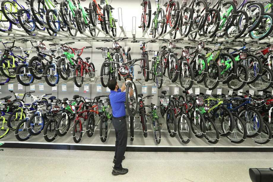 Academy Sports & Outdoors, 9734 Katy Freeway at Bunker Hill, Team Leader Dhiraz Hussain restocks bikes Thursday, June 1, 2017, in Houston. Academy Sports & Outdoors, a sports, outdoor and lifestyle retailer with more than 230 stores in 16 states, is one of Houston's largest private companies.  ( Steve Gonzales  / Houston Chronicle ) Photo: Steve Gonzales, Staff / © 2017 Houston Chronicle