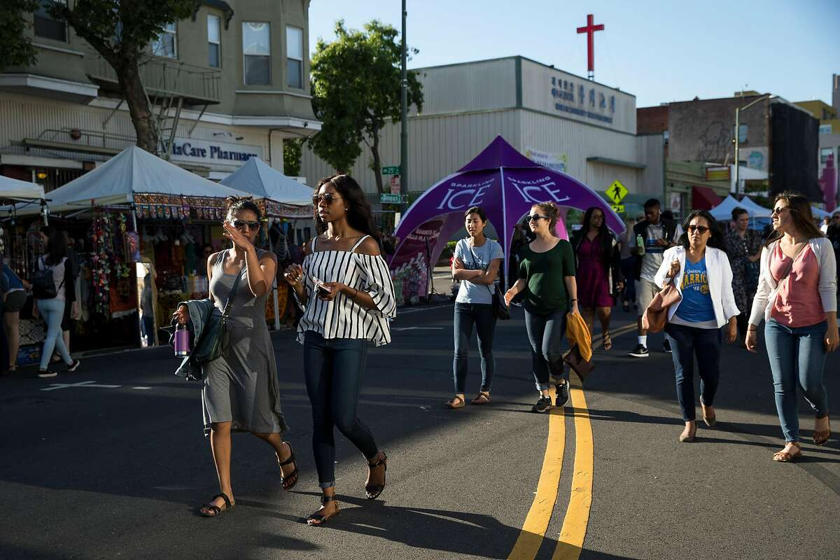 Attendees of the Oakland First Fridays street festival walk along Telegraph Avenue during the event on June 2, 2017.