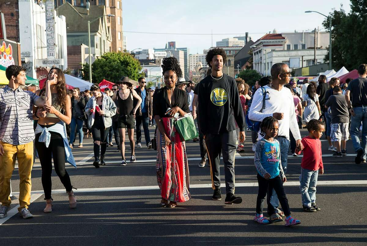 Imani Triplett and Marcellus Demer (at center) walk along Telegraph Avenue with other attendees of the Oakland First Fridays street festival on June 2, 2017.
